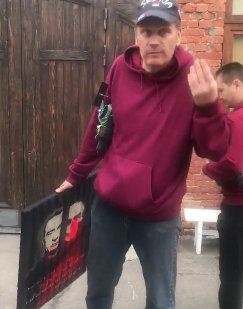 Einer der Angreifer mit einem mit Farbe überschütteten Bild des Künstlers Vasiliy Slonov.